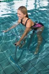 Fit happy blonde using underwater exercise bike