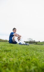 Football player in blue taking a break on the pitch