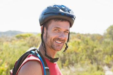 Fit cyclist smiling at the camera on country terrain