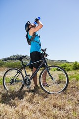Fit cyclist riding in the countryside taking a drink