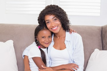 Pretty mother sitting on the couch with her daughter smiling at