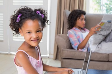 Cute daughter using laptop at desk with mother on couch