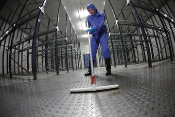 worker in uniform cleaning floor in empty storehouse