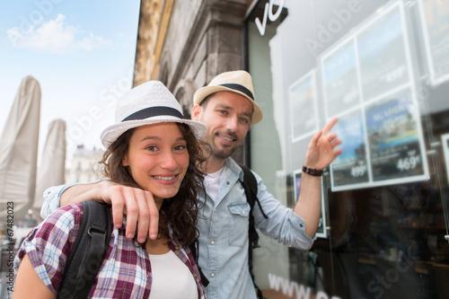 Młoda szczęśliwa para przed agencją podróży