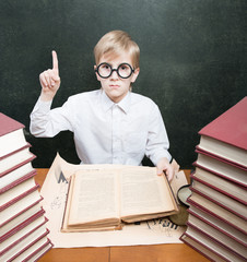 Retro style boy with old book raising index finger up