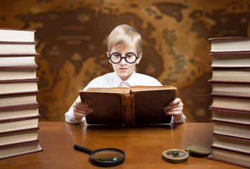Retro style portrait of a reading boy against an old world map