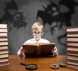 Retro style boy reading the old book of spooky stories
