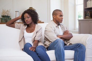 Unhappy couple not speaking to each other on sofa