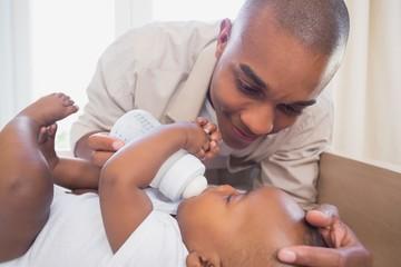 Happy father feeding his baby boy