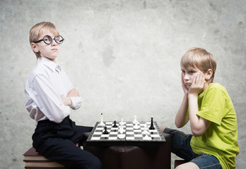 Boy and nerd playing chess