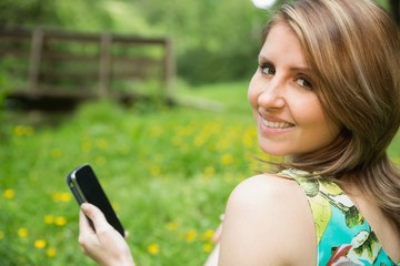 Smiling woman text messaging in field