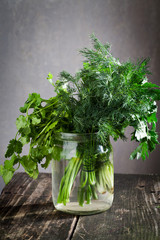 dill with parsley and coriander in a jar on a wooden board