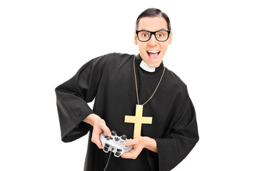 Joyful priest holding a gamepad