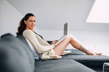 Beautiful young lady on sofa with a laptop