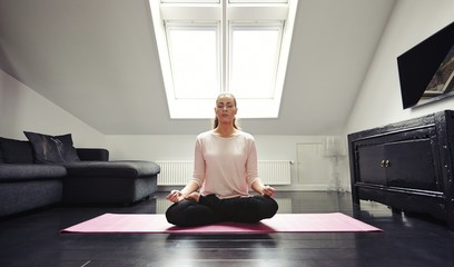 Young woman meditating in lotus position at home