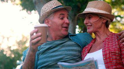 Happy tourist couple sitting on bench holding map