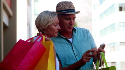 Happy couple on day out shopping looking at smartphone