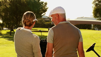 Couple standing on the golf course looking around