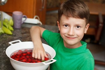 Boy take out fresh cherry from bowl
