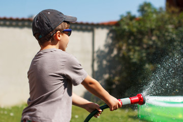 Little boy watering with hose