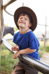 Little caucasian boy laughing on farm