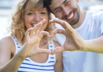 Happy love couple outside showing heart with fingers