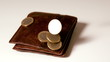 Euro coins falling over brown leather wallet on white surface