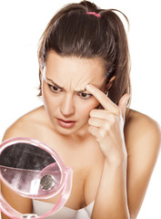 disappointed young woman touching her eyebrow in the mirror