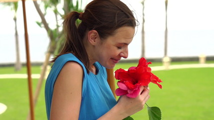 Happy woman with beautiful flower in garden, super slow motion