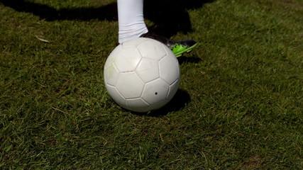 Football player kicking the ball on grass