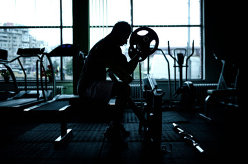 silhouette of an athletic man working out at gym