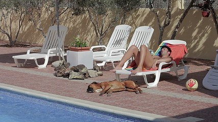 Man sleeping with dog by the pool