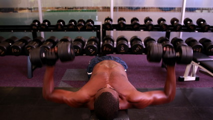 Fit shirtless man lifting dumbbells lying on bench