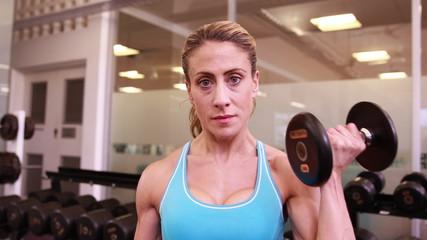 Super fit woman lifting dumbbells at crossfit