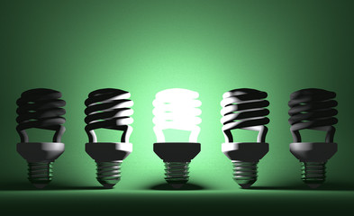 Glowing spiral Light bulb among dead ones on green