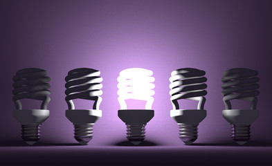 Glowing spiral Light bulb among dead ones on violet