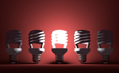 Glowing spiral Light bulb among dead ones on red