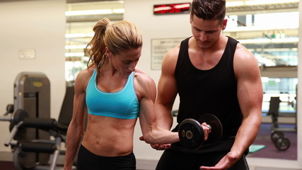 Woman lifting dumbbell with her trainer at crossfit session