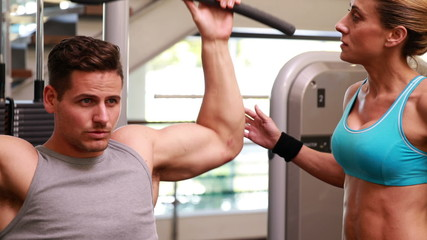 Fit man using the weights machine for his arms while trainer sup