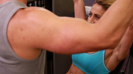 Fit woman using weights machine for arms with her trainer