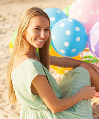 Woman on the beach holding colored polka dots balloons