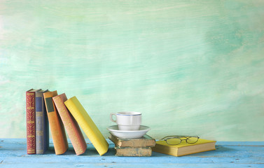 vintage books with coffee cup, spectacles, grungy background, fr