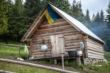 Wooden kolyba hut with a Ukrainian flag