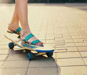 Teen girl on longboard on the street