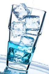 Glas mit Eiswürfel und blauerm Getränk