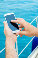 Male hands using smartphone on sailing