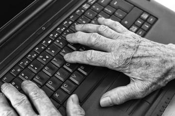 Elderly hands on keyboard of laptop.