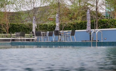 Tables and chairs at swimming pool