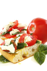 Sandwich with tomato, cheese and basil.