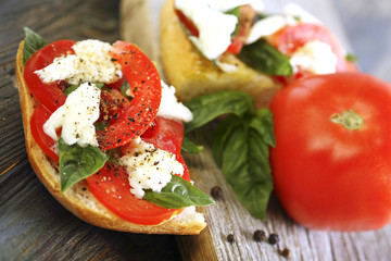 Ciabatta with tomatoes, cheese and basil close-up.